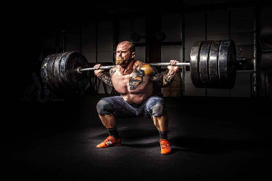 man strength training with heavy squats