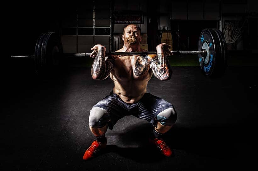 man strength training with barbell