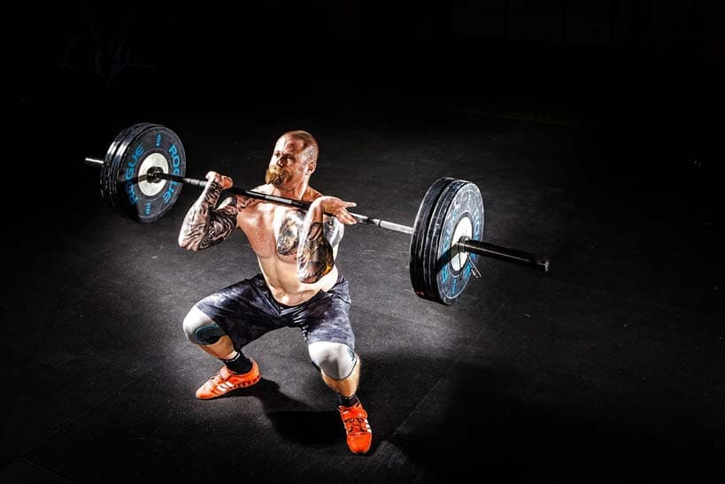 man squating with barbell strength training