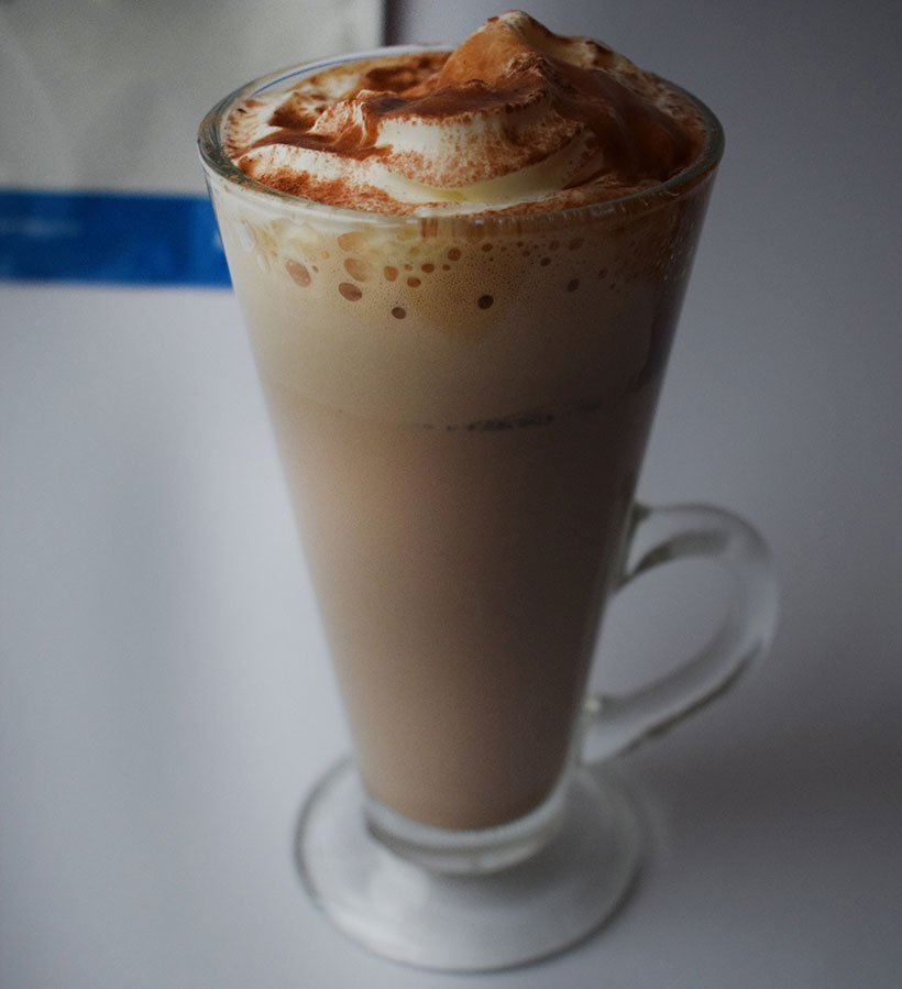 Myprotein protein hot mocha in glass with cream, syrup and powder